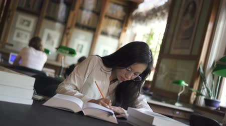 téma : Attractive young woman is writing, reading book sitting at table in library, busy female student lawyer wearing eyeglasses is studying topic, taking notes in notebook during educational day. Concept: learning, university, researching theme. Dostupné videozáznamy