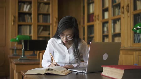 stříbřitý : Diligent female student biologist writing at table with book and laptop in library, attractive brunette wearing eyeglasses is making notes, looking at text at desk with silvery device in reading room. Concept: university, technology, occupation.