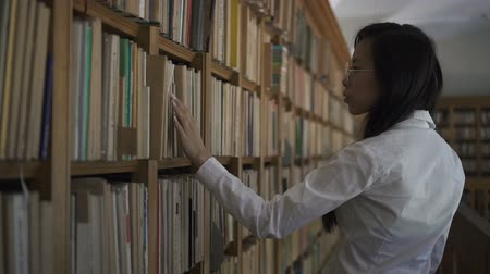 tome : Young asian biologist student in white shirt taking old book from a bookshelf in the library. Indoors. Portrait.
