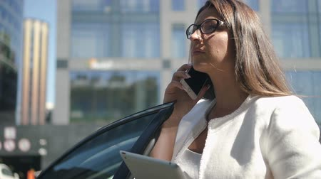silvery : Young busines lawyer is making call, holding tablet standing on city street, beautiful brunette is talking on phone, looking at gadget screen, leaning on black car on summer day. Concept: business person, successful, technology.