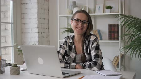 przedsiębiorczość : Female business owner programmer smiling in the office, working on laptop. Woman in glasses and grey checkened shirt sitting at the working table with brand-new computer on and posing for annual photo, looking to camera. Portrait.