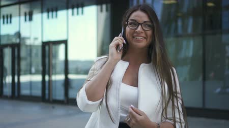 banqueiro : Beautiful young chief banker woman is talking on phone standing on background of office building, elegant American lady wearing eyeglasses is making call, having time on metropolis street. Concept: communication, business person, corporate. Stock Footage