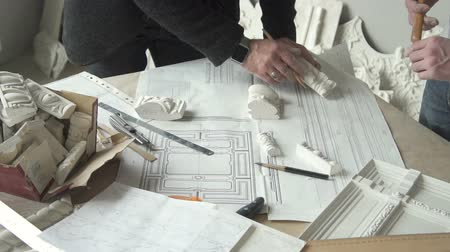 crépissage : Hands of two male architects working with white plaster molding samples and blueprints on the table in studio. Indoors.