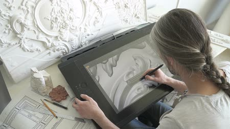 restorer : Architect restorer working with graphic tablet sitting at table in modern office, experienced master enters image created by hand in PC at desk with white plaster decorations. Concept: designing, technology, occupation.