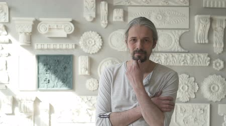 глина : Mature male sculptor standing in his studio with molding samples and touching his beard looking to the camera. Indoors. Portrait. Straight shot.