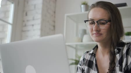 facetime : Portrait of young female looking at invest monitor screen in home interior, beautiful businesswoman in casual clothes is working with laptop, smiling, sitting at table in a modern apartment. Concept: success, innovation, lifestyle. Stock Footage
