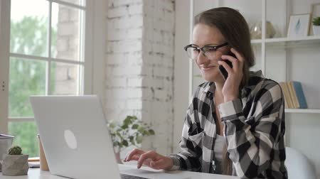facetime : Young business owner woman working with laptop, talking holder phone in home office, businesswoman is making call, looking at pc monitor, sitting at table in light room with window and book shelves. Concept: professional, successful, business technology.