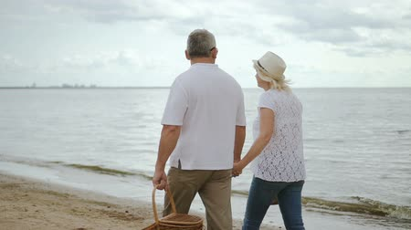 emekli : Elderly woman and male pensioner moving along seaside. Mature man and senior female spending weekend together.