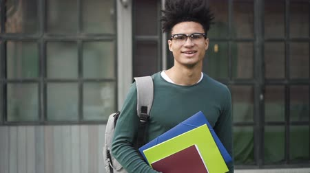 латина : Confident african-american student is standing on front of campus. Attractive hispanic man in black glasses smile in camera and make you smile back. Smart and creative guy that looked relaxing after working.