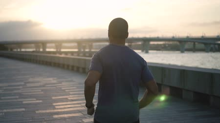 correre via : Sportive, actice, young man in slow mo make joggong across the bridge away from camera. Fitness lifestyle of masculr athlete on the wonderful sunrise backstage. Feel attractive freedom from this strong runner on high speed. Filmati Stock