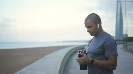 cansado : Sweaty runner drinking water through the strong exercising and healthcare training. Active, muscular, athletic man in casual workout use fitness bottle for resting from bodybuilding and listen music. Stock Footage