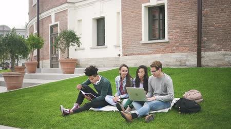 výhoda : Mixed-race students siting on the pleasant grass behind campus and discuss networking technology, computer, media and advantage of its using at university. Friendly team is surfing in the internet and resting together.