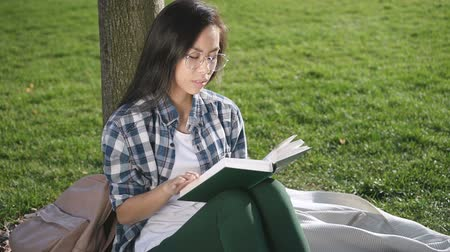 relance : Pretty cheerful girl is reading in the park. Pleasant korean female in round glasses is sitting on the tree and attentively looking in the book. Slowmotion video and pensive glance of young long haired lady.