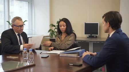 solicitor : African-american lawyer presenting legal document to senior businessman and young chief executive. Businesspeople arguing concerning contract detail and using competent advice. Stock Footage