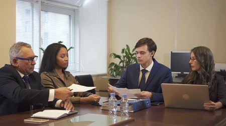 comparar : Mature agent and young woman are very attentive looking through the papers to make sure it all right. They are sitting in the office and planning signing documents after cheking all details of contract. One lawyer also compare information with the compute Stock Footage