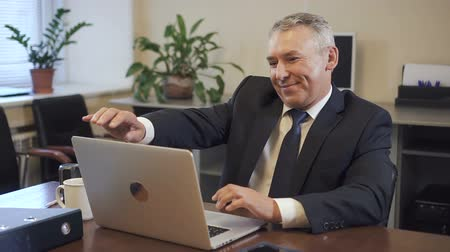 administrador : Senior entrepreneur in suit working on laptop computer in office. Mature ceo looking to camera and smiling on workplace in consulting company. Portrait. Slow motion.
