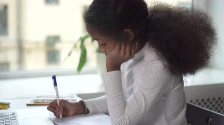 çok güzel : Mixed-race mid-adult girl working at her homework. African daughter use laptop to improve quality of knowledge. She is very serious and not smiling while sitting at the desk and getting mail from teacher.