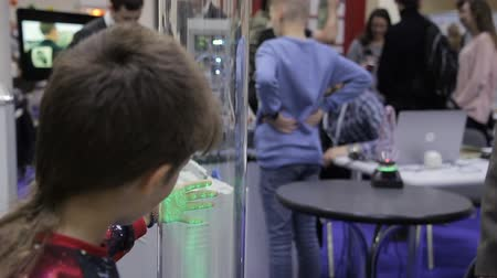 konu : Moscow, Russia - October 6 2016: Annual Science Festival Nauka0 : Children and adults attend exhibition of scientific inventions indoors. Interested people view and touch objects, walking around room. Boy stands near glass subject and touches it with ha Stok Video