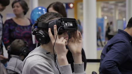 Moscow, Russia - October 6 2016: Annual Science Festival Nauka0 : At exhibition of modern technologies teenager looks into virtual reality glasses. Boy is studying computer technologies that offer games with full immersion in space.