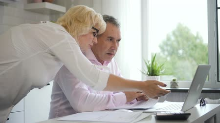 portátil : Mature woman and male pensioner discussing investment at home. Senior couple using computer and paper graph to research financial rate.
