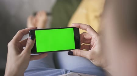 wi fi : business asian woman holding a online mockup green screen phone, on couch at home, in her hands and watching app wi-fi tv and analytical graph. Concept: keying, green screen