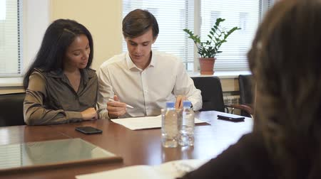 realtor : Lovely multiethnic couple in real estate agency office signing mortgage contract. African woman and caucasian man buying Stock Footage