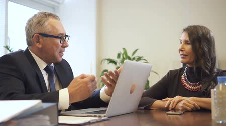 people talking : Senior man and mature woman discussing mortgage details. Businessman in glasses sitting at desk and using laptop computer and businesswoman taking to him.
