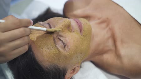 így : Female master applies special healthcare, medical mask on face to make healthy rejuvenation of all skin so it can looks young and fresh. Cosmetologist try do very accurate and smooth movements not to damage beauty. Stock mozgókép