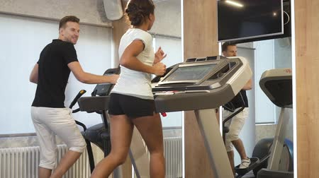 cardio : Mixed race couple have training in gym. African woman running on treadmill and talking to caucasian man on eliptical equipment. People laughing and smiling. Slow motion.