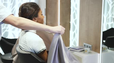 dressing room : Young hispanic woman comes to hairdressing specialist to shape and improve her haircut. Female master cover pretty client with cape to protect from garbage. She is looking confident and friendly straight in the mirror.