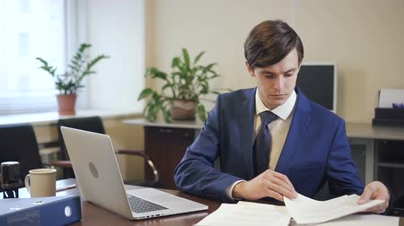formální : Businessman working on laptop and with paper document in modern office. Young man in business suit is busy looking for information on the project. Portrait.
