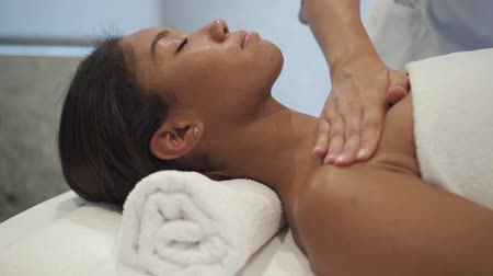afro americana : Therapist massaging shoulders of african customer in spa center. Woman with closed eyes lying on back on massage table during professional healthcare procedure. Slow motion.