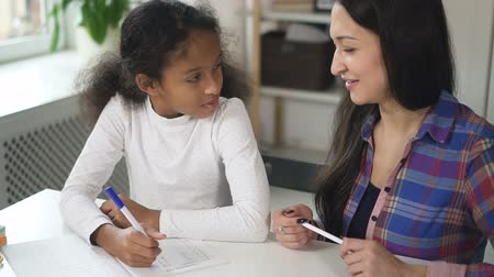репетитор : Happy and confident adult mixed race teacher helping her black young school student teacing her as a woman tutor learning knowledge. Medium shot of creative mother helping her daughter working together on development indoors sitting on table in slow motio