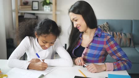 латина : Adult mixed race woman teacher sitting and talking to american black student child in school class during day. Mother and daughter of different ethnicity are learning to draw together. Стоковые видеозаписи