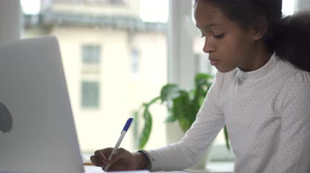 conveniente : Mixed-race mid-adult girl working at her homework. medium shot of happy black girl at home Stock Footage