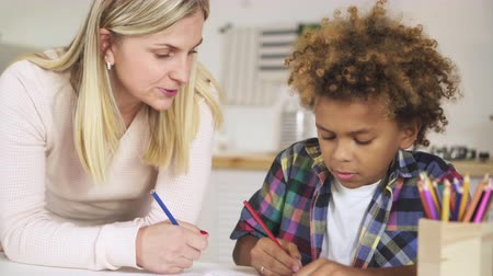 foster : Single and beautiful young woman mum helping to her smart son prepare school homework. They sitting together over notebook behind table or desk inside bright light living room with pencil in hands