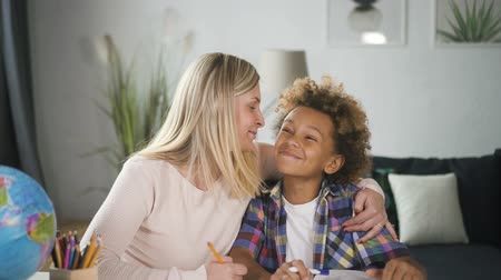 task : Beautiful and blond hair woman mama looking at her lovely, happy and exited son. She helping to her boy prepare school homework, they laughing and clapping in hands making wide Hollywood smile