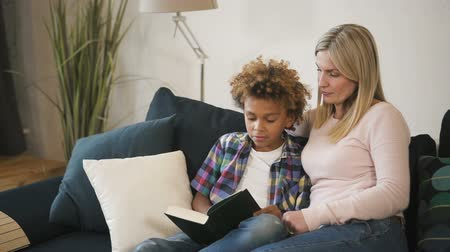 pré adolescente : Calm and blond hair woman mama, wearing in casual wear sitting on cozy comfort sofa inside bright light living room. She spending free time with her charming and sweet son, reading interesting books