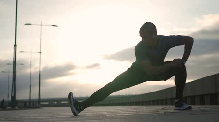 feliz : African american jogger stretching legs for work out. Sportsman doing warm up exercise for intence running. Concept of: motivation, cardio, training. Portrait. Stock Footage