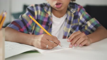 deha : Cropped and close up view of smart, focused and concentrated little boy with color pencil in hand. He sitting behind desk inside bright light room and preparing difficult lessons to his homework