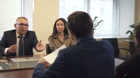 solicitor : Negotiation briefing with multiethnic partners in office conference room. Lawyer giving contract draft to mature businessman and african-american businesswoman. Slow motion.