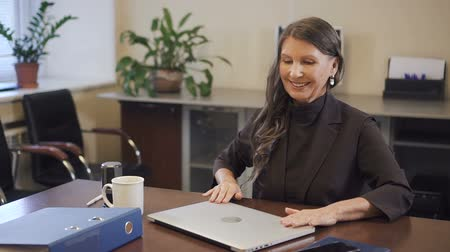 conferencing : Experienced mature businesswoman finishing working on laptop computer in office. Senior leader looking to camera and smiling. Portrait. Stock Footage