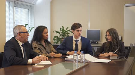 kongres : Mature businesswoman presenting project to multiethnic colleagues using laptop in office. African-american woman, senior businessman and lawyer listening to her.