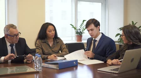 прокат : Briefing in multiethnic company cozy office conference room. Mature businesswoman showing research results on laptop computer screen. male lawyer checking contract, senior businessman using tablet and african-american intern taking notes.