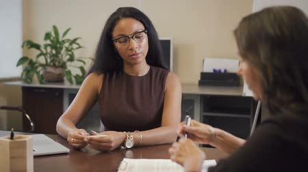 rekrutacja : African-american solicitor presenting contract to mature female customer. Lawyer explaining details of property buying and senior woman signing document.