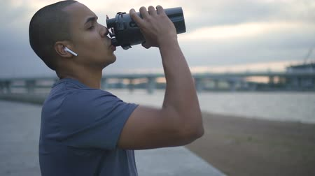 African american athlete drinking water during running workout. Ethnic sportsman in earphones holding bottle with beverage standing on urban embankment. Portrait.