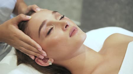 хозяин : Qualified master making face lifting for attractive and peaceful woman, who came on resort center for anti-agin massage. She lying on spa bed inside light salon interior with closed eyes