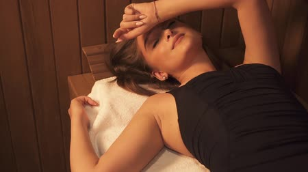 bodywarmer : Beautiful isolated hot woman is lying on benc at steam room on white towel for skin wellbeing therapy. Health fitness lifestyle at hotel sauna os spa thermal resort. Clean wellness and medicine wellness. Stockvideo