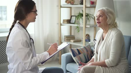 Retirement woman talking with practitioner in white medical coat. Doctor notes information in blank while they sitting on couch in bright interior with soft natural light and discussing complaints Stock Footage