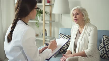 назначение : Young doctor is discussing with senior patient diagnosis and healthcare treatment. Medical specialist is attentively and serious listening to aged woman for high professional consulting and helping with prescription.